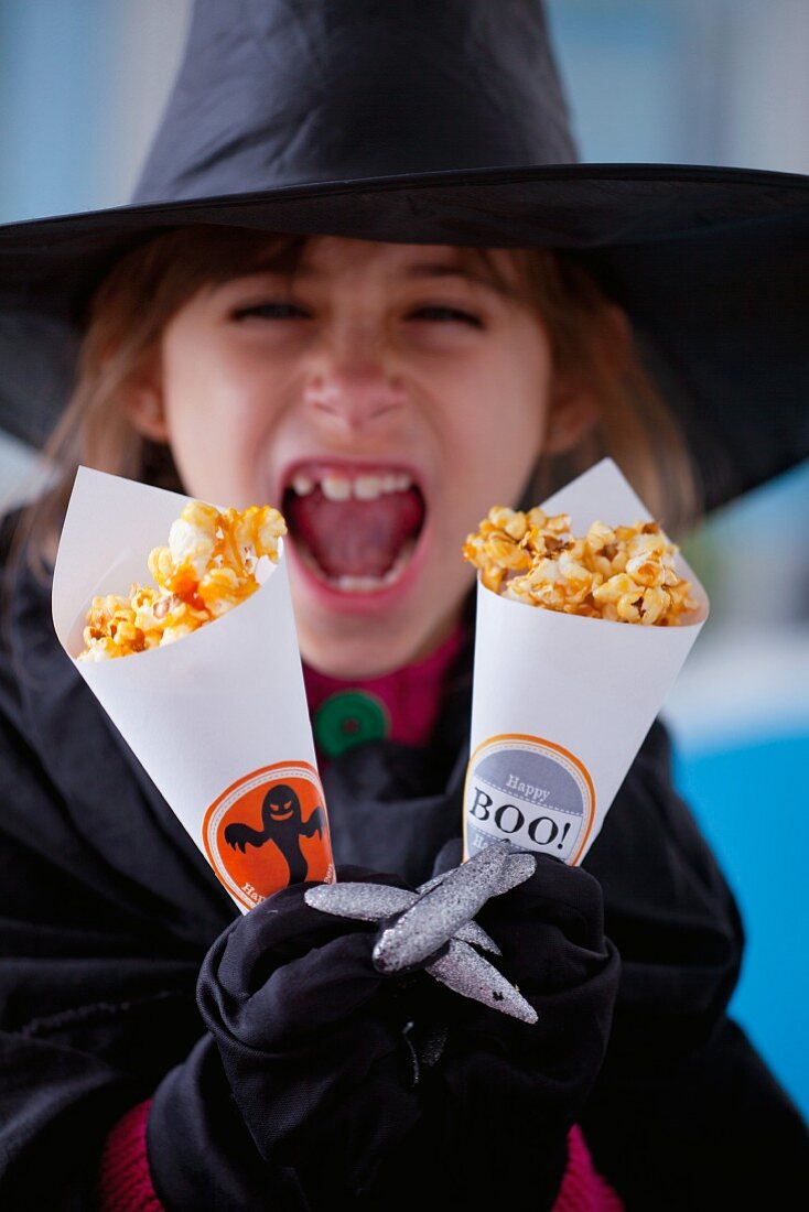 A girl holding paper cones of caramelised popcorn for Halloween