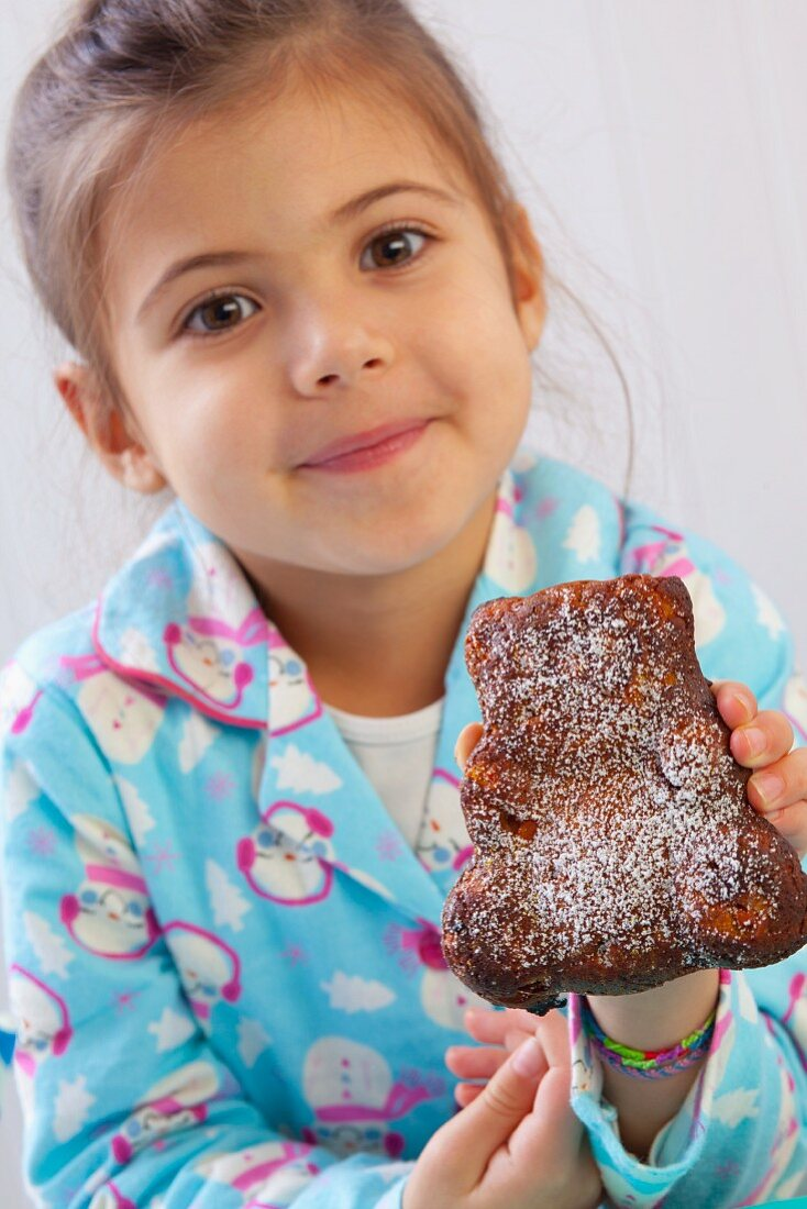 A girl holding up a bear-shaped carrot cake