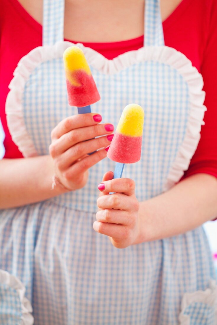 A woman holding two home-made ice lollies