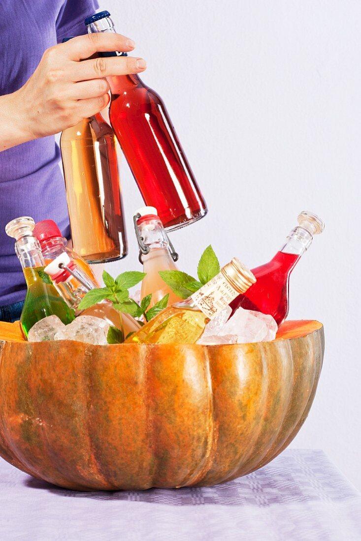 A hollowed-out pumpkin as a bottle cooler