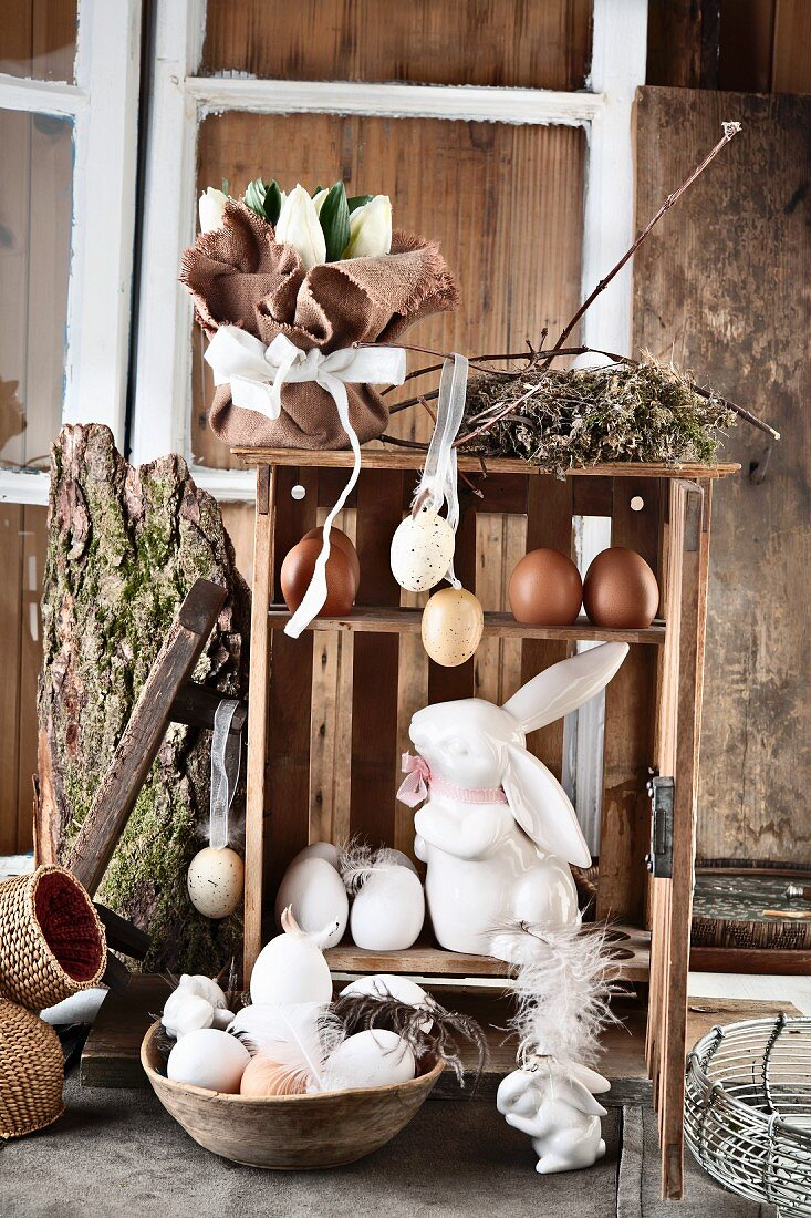 An antique egg box made of wood, with eggs and a porcelain hare