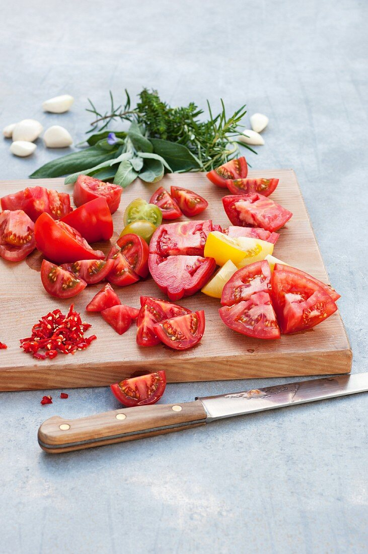Tomatoes cut into small chunks on a wooden board