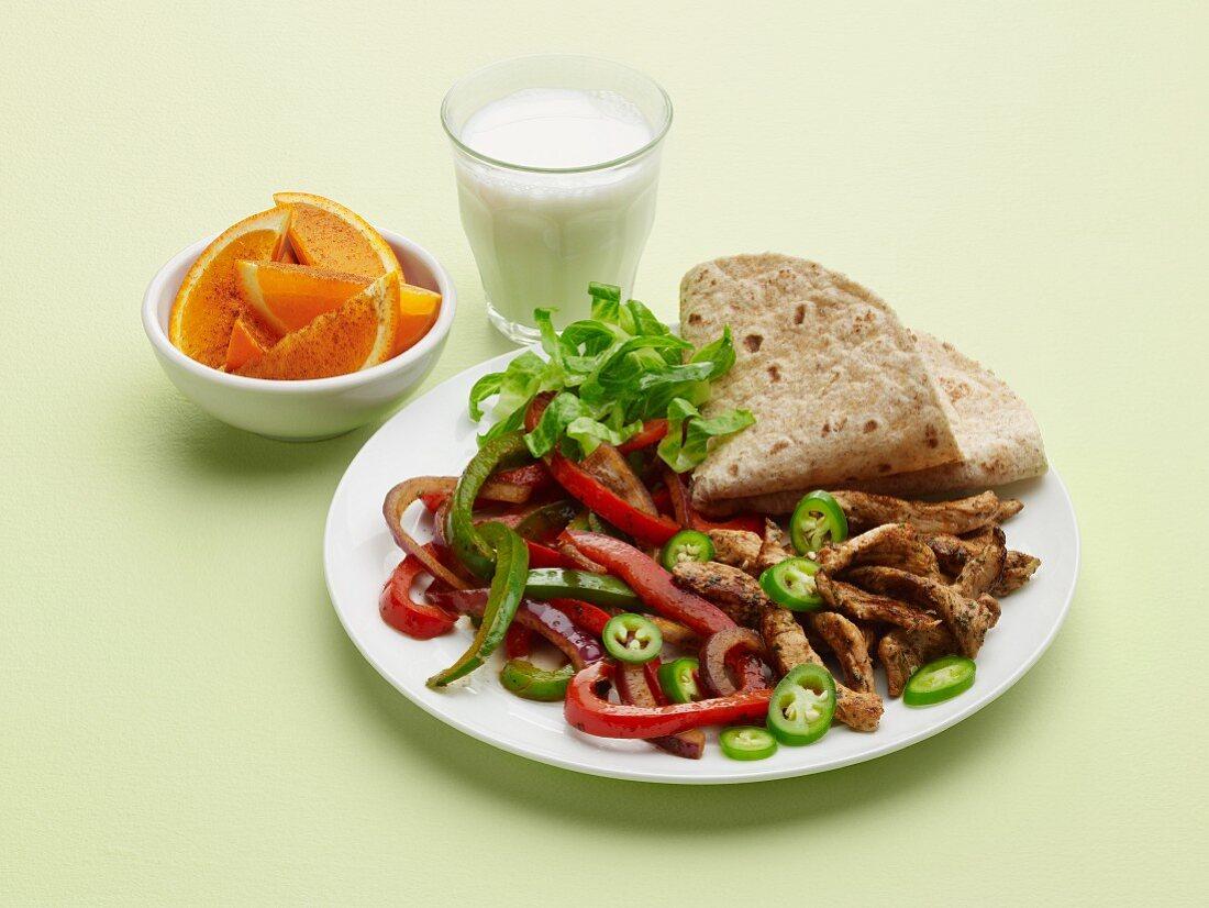 Pork Fajita Plate with Orange and a Glass of Milk