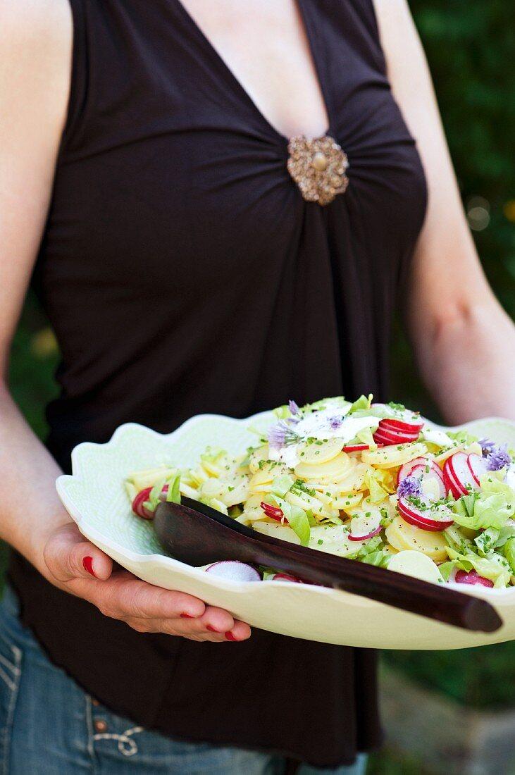 A woman serving a large bowl of potato salad