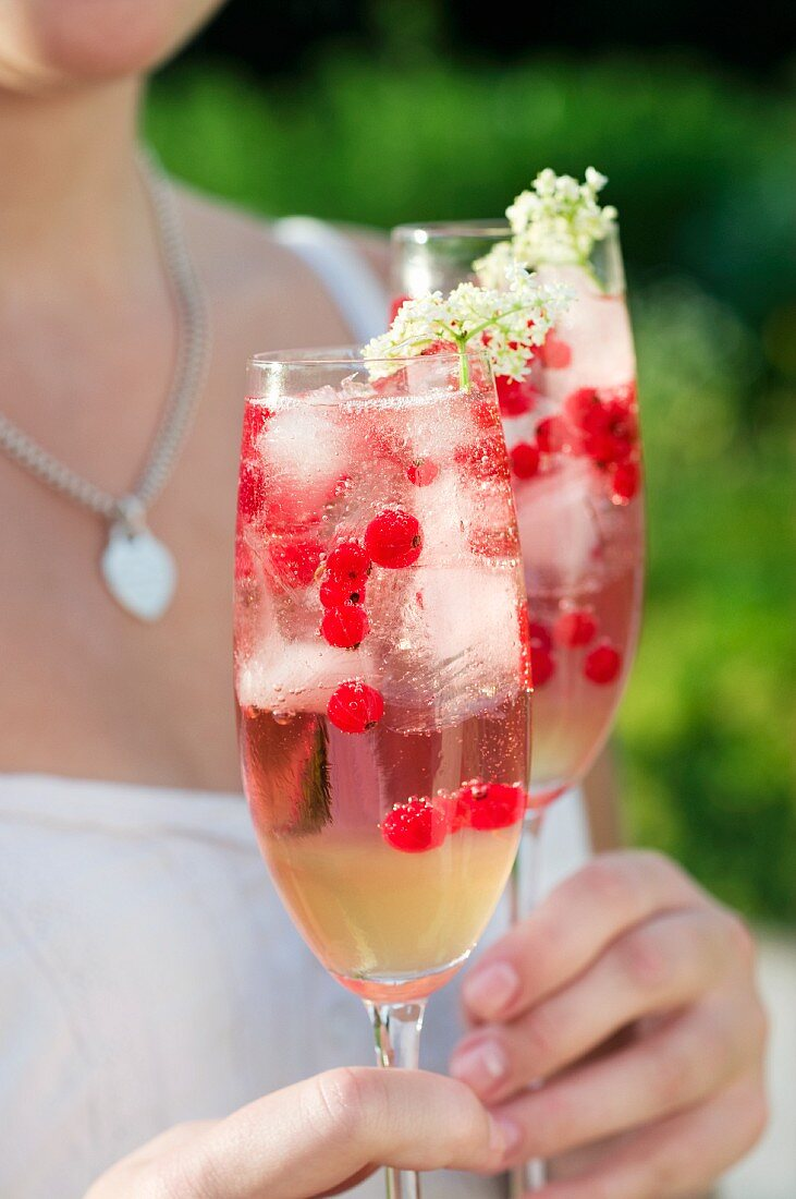 A woman holding two glasses of elderflower fizz with redcurrants