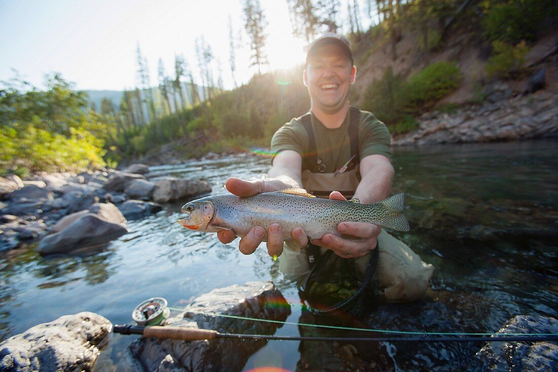 An angler in the river proudly holding up a freshly caught trout