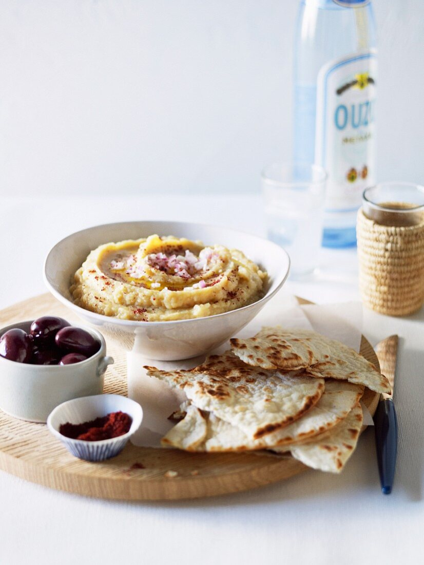 Yellow split pea dip with unleavened bread and olives