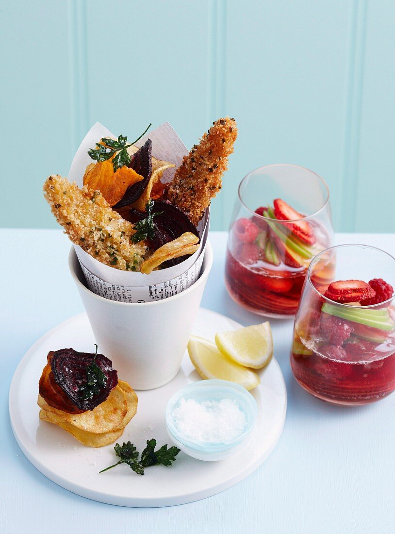 Fish and chips with vegetable chips and fried parsley served with fruit punch