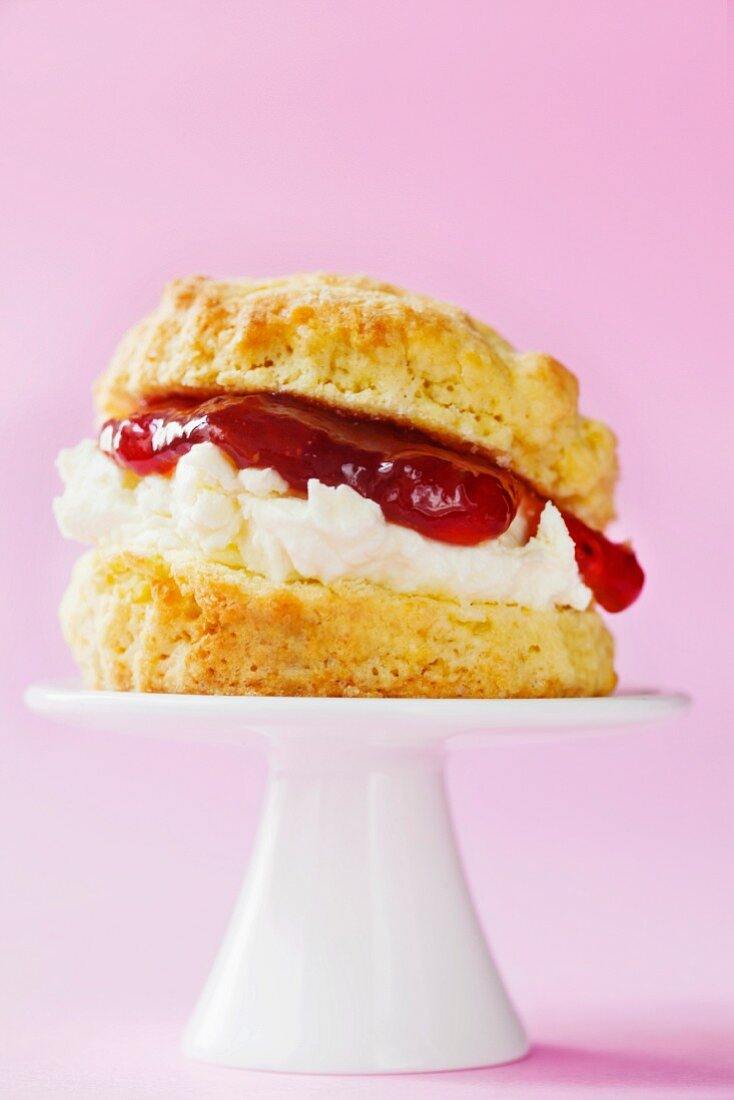 Scone with clotted cream and strawberry jam on a mini cake stand