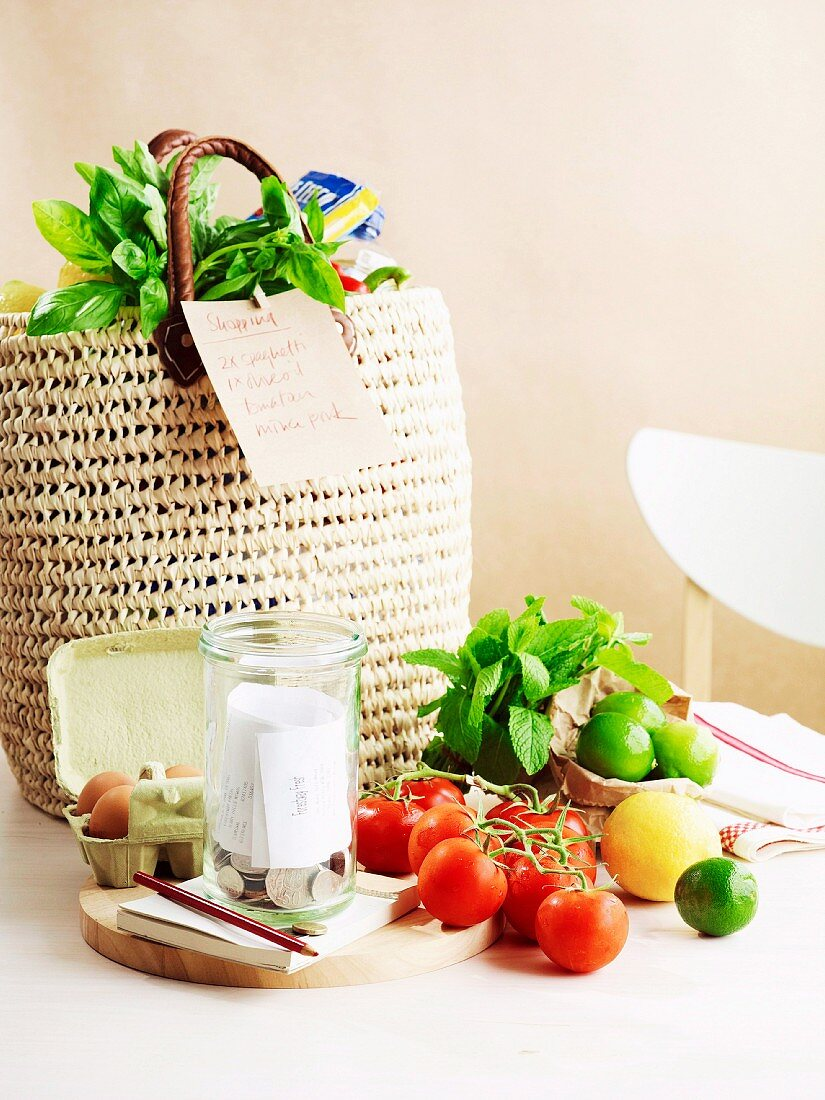 A wicker shopping bag with a list, tomatoes, limes, eggs, coins, a notebook and a pen