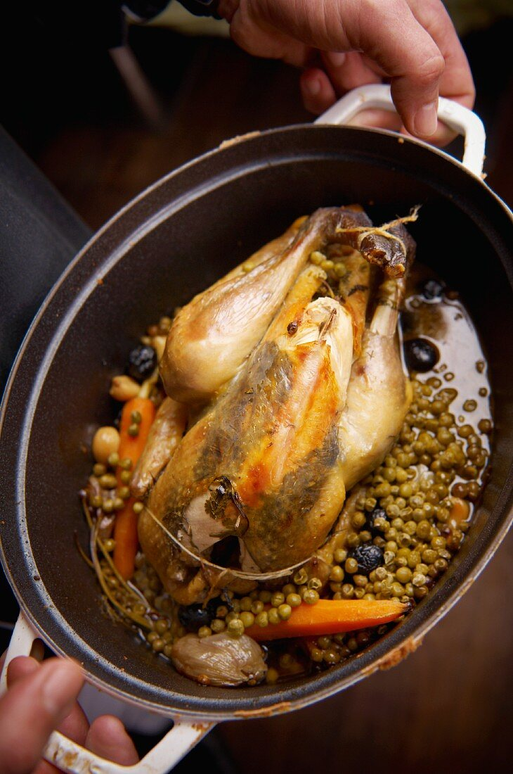Guinea fowl stuffed under the skin, cooked with peas, carrots and olives