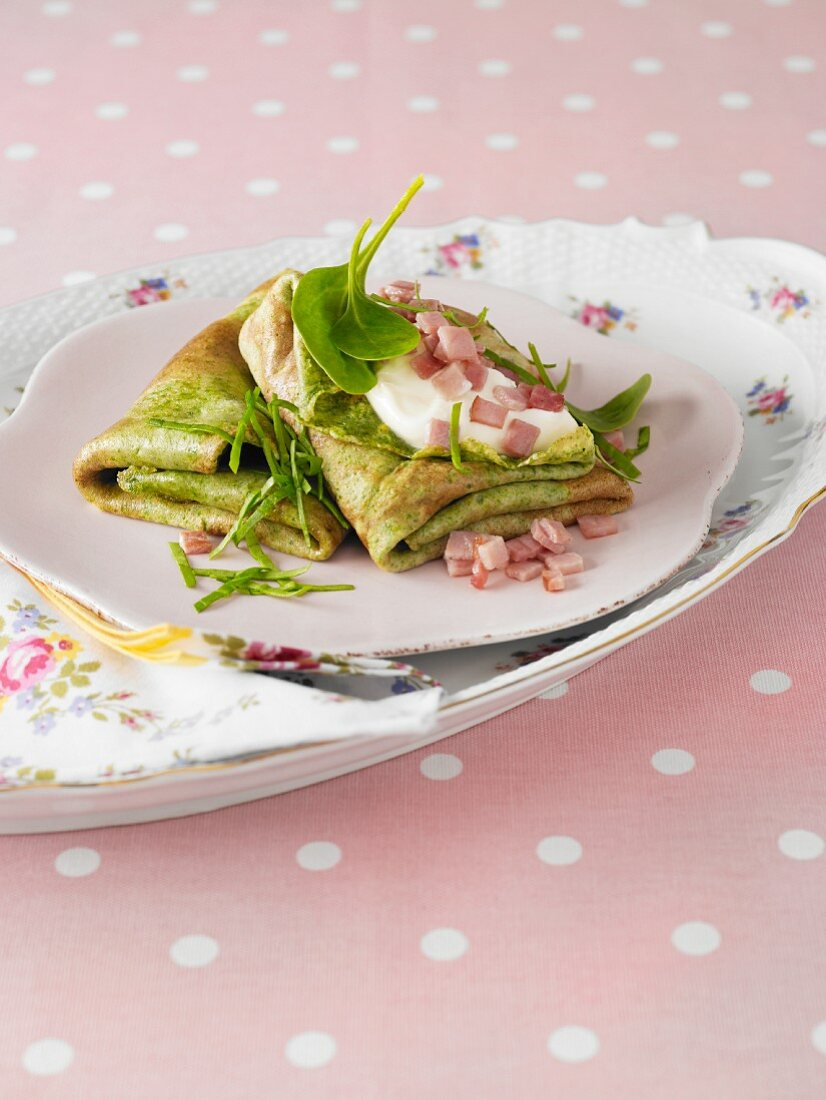 Spinach pancakes with sour cream and diced ham