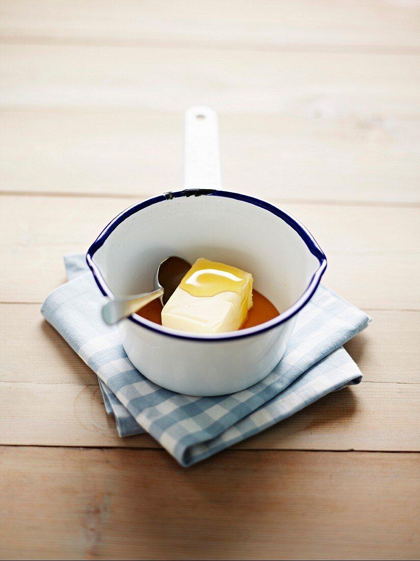 Block of butter melting in an enamel saucepan