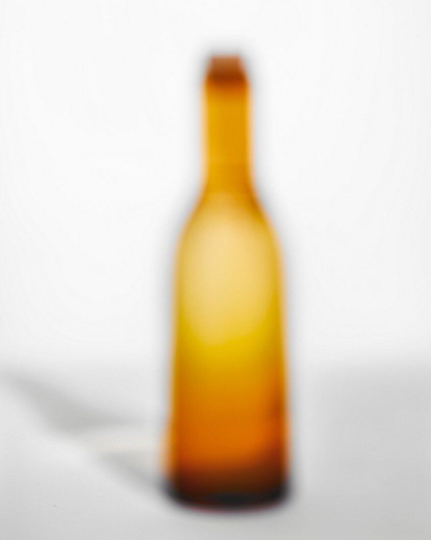 An out-of-focus orange bottle with cork on a white background