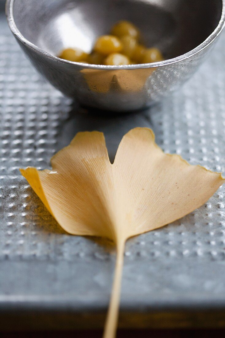 A gingko leaf and a silver bowl of gingko nuts