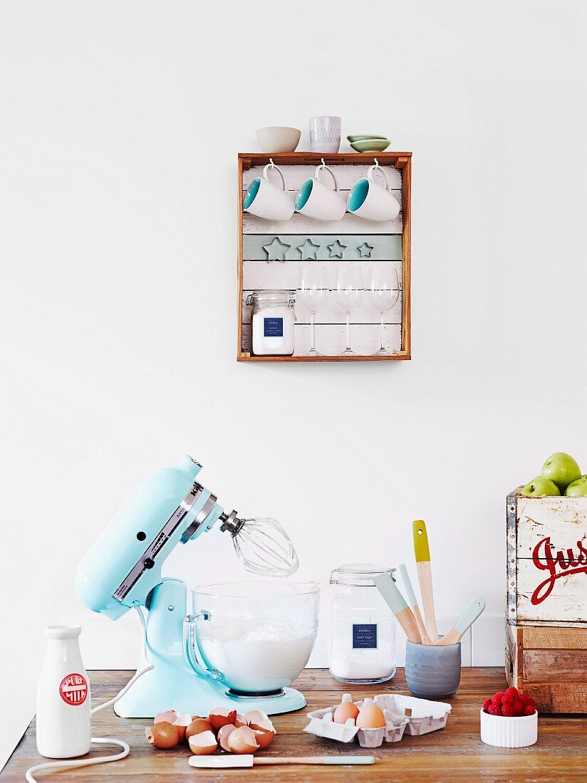 Retro mixer and cracked eggs below wooden crate mounted on wall with bottom slats painted white and turquoise and hooks for cups and pastry cutters