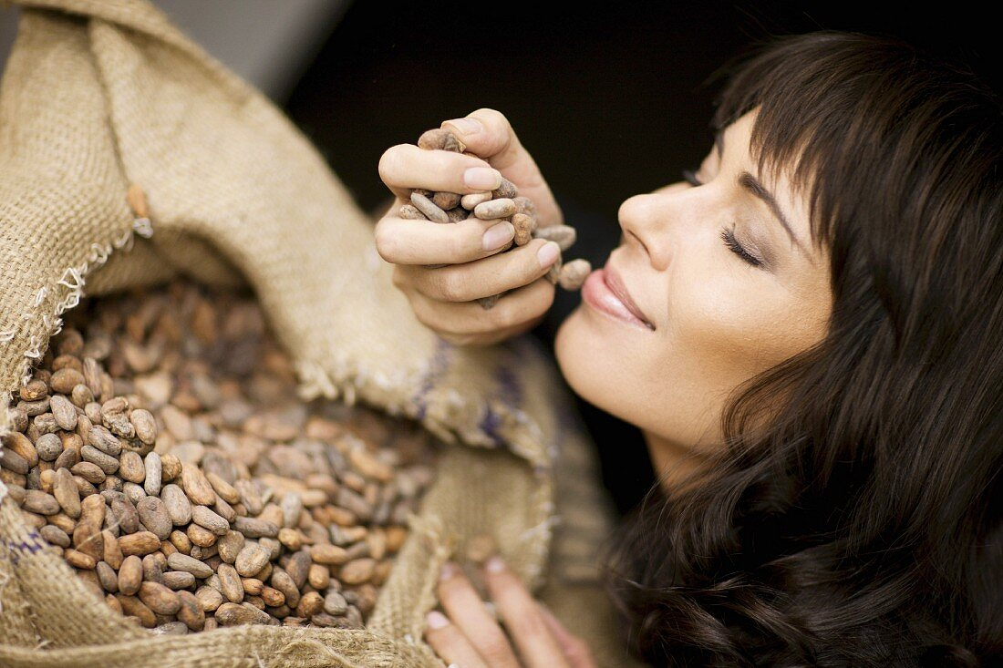 A woman checking the aroma of fresh cocoa beans
