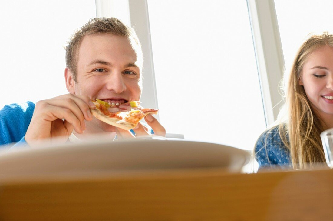 A young man eating pizza