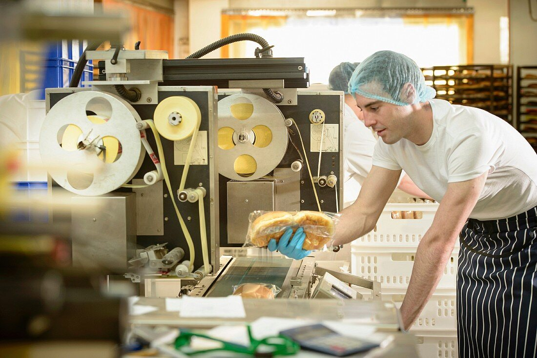 A worker in a bakery operating the packaging machine