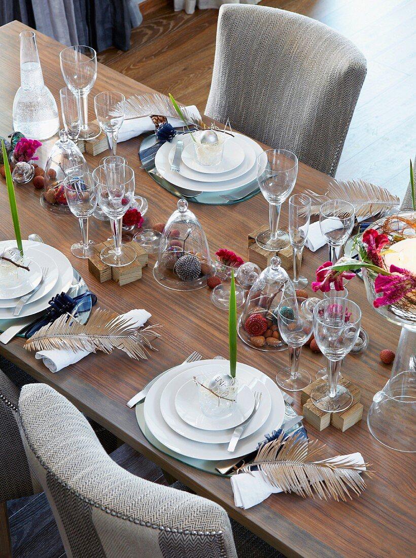 Gedeckter Tisch für Weihnachtsessen mit Blüten, Federn, Nüssen und Dekokugeln
