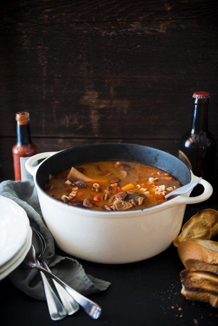 A hearty bean soup with lamb shank in a casserole pot