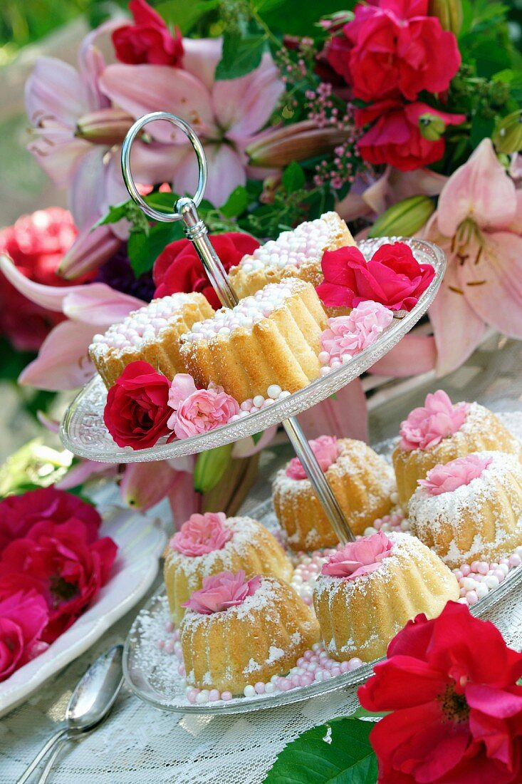 Small Bundt cakes with sugar pearls and rose decorations on a tiered cake stand