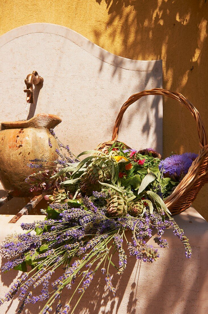 A basket of lavender, vegetables and flowers on a well in Provence