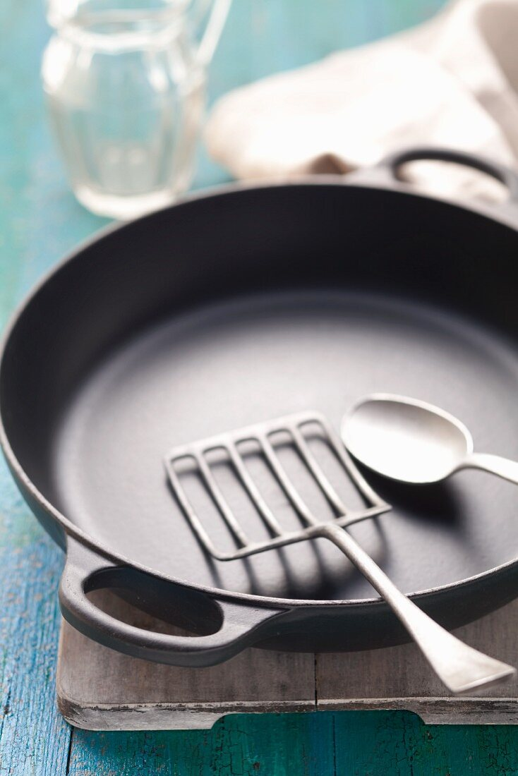 An empty, black frying pan with a frying spatula and a tablespoon