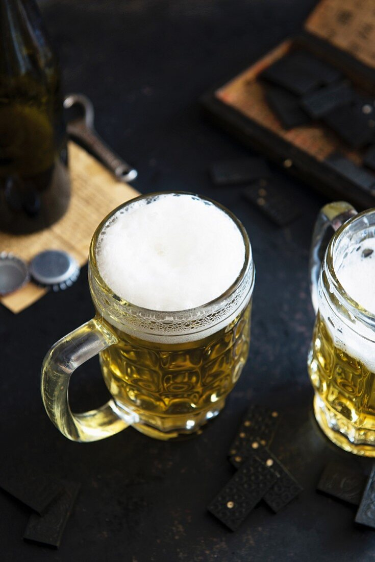 Two glasses of beer on a table with dominoes