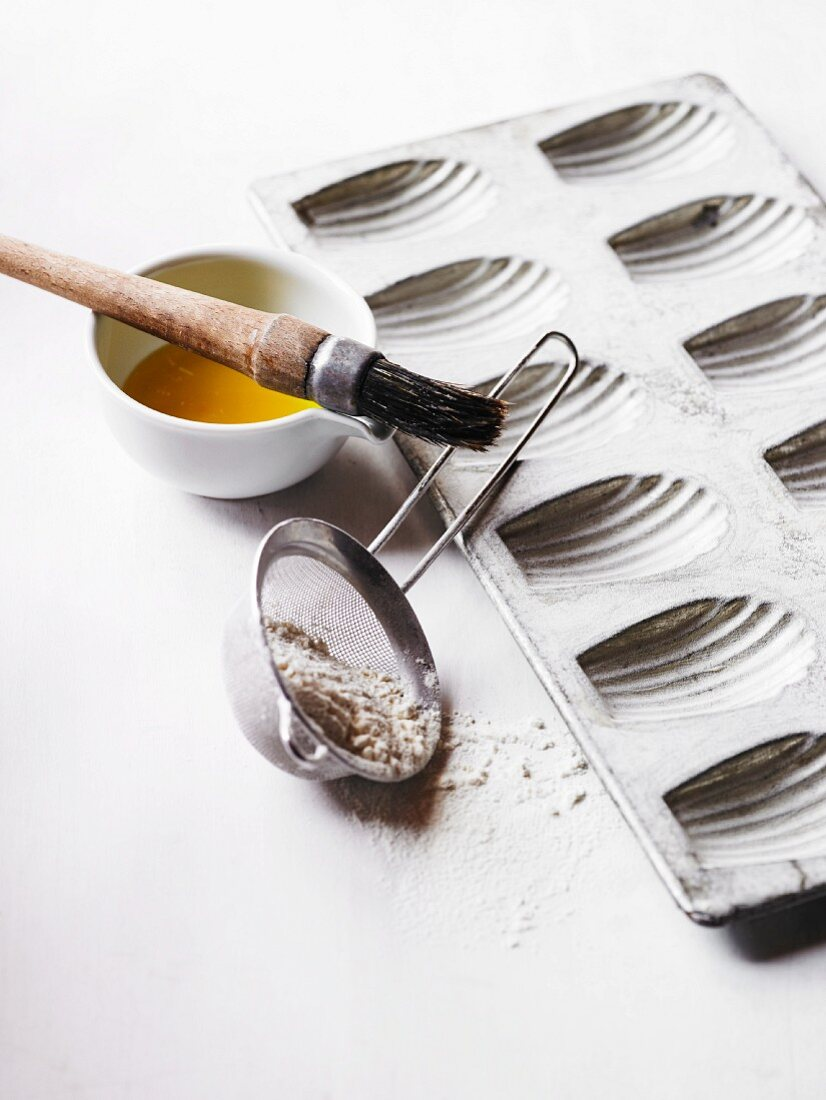 A baking tin for madeleines, flour, egg yolk and a pastry brush