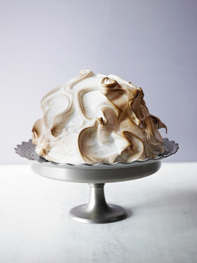 Blueberry cake coated with meringue, on a cake stand