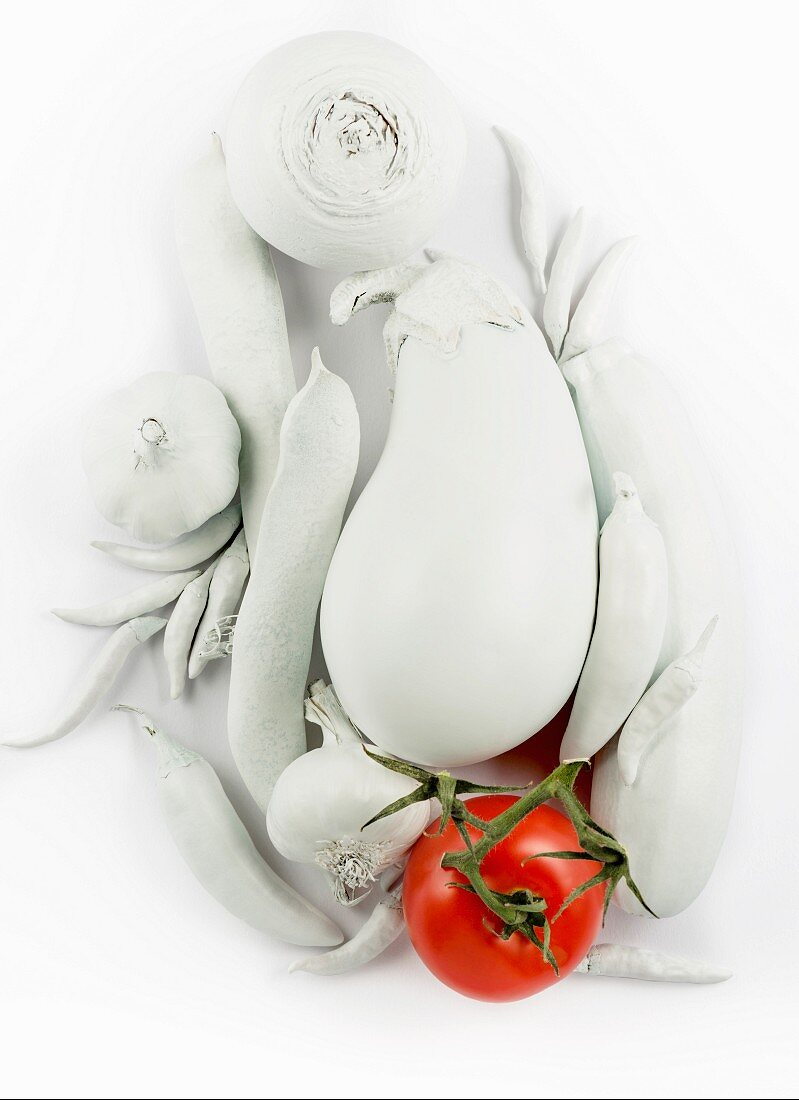 A still life in white, featuring vegetables, with a red tomato