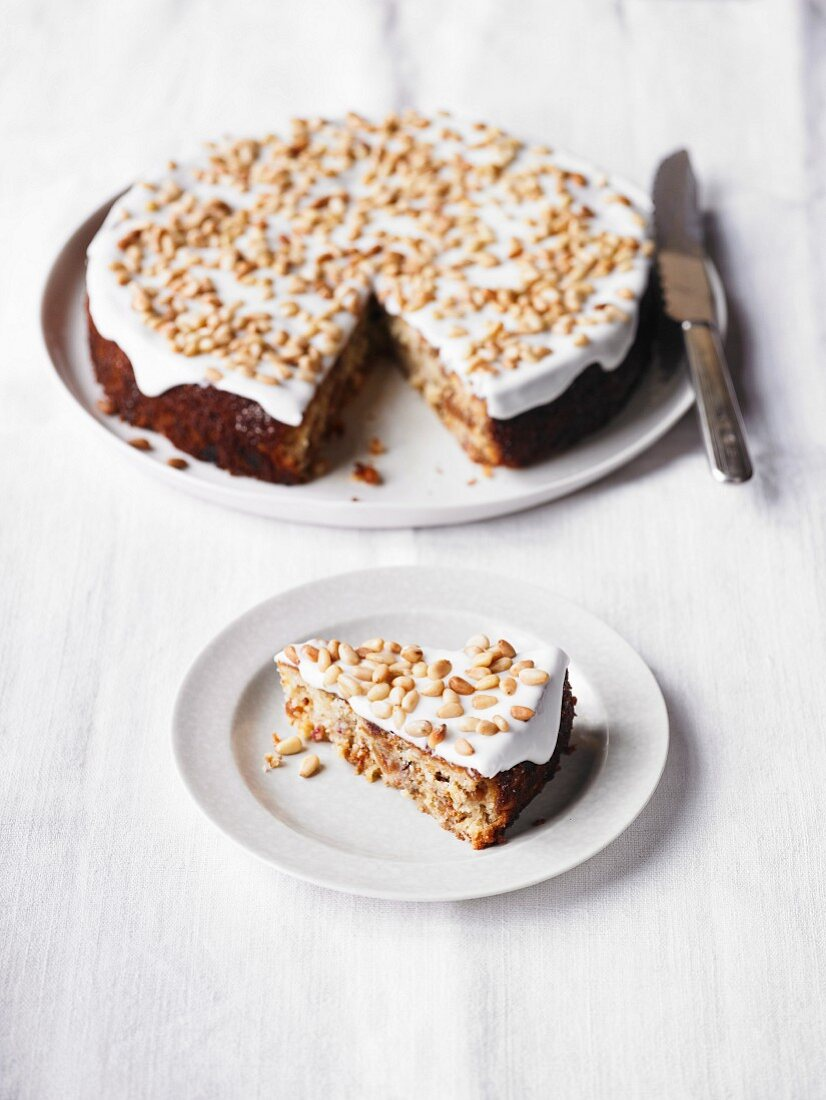 Fig & ricotta cake with pine nuts, one slice cut