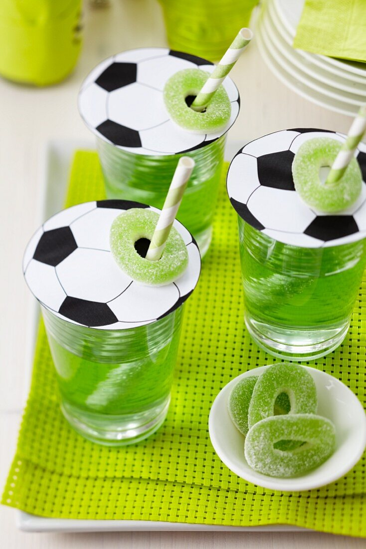 Football-shaped paper glass covers with straws and jelly sweets