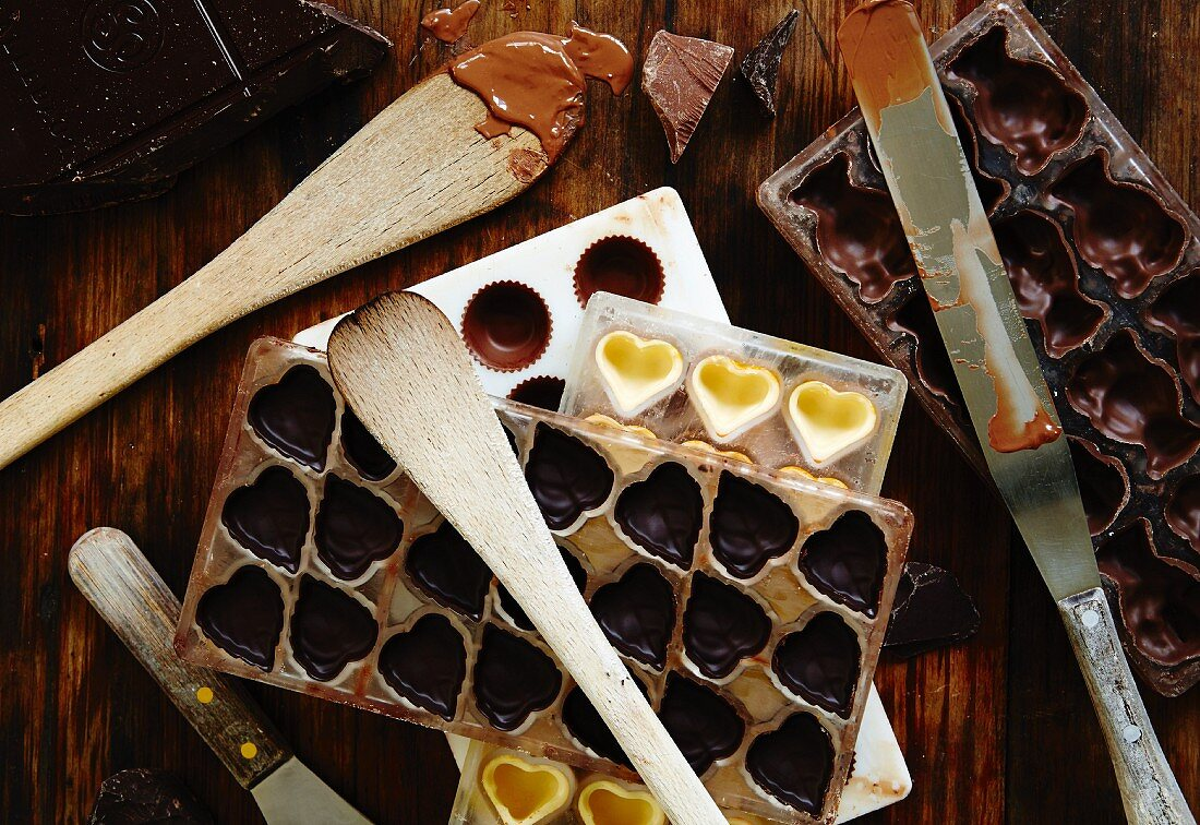 Assorted moulds for chocolates, a knife and wooden spoons