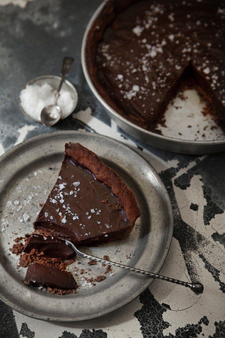Dark chocolate truffle cake sprinkled with salt, a slice on a silver plate