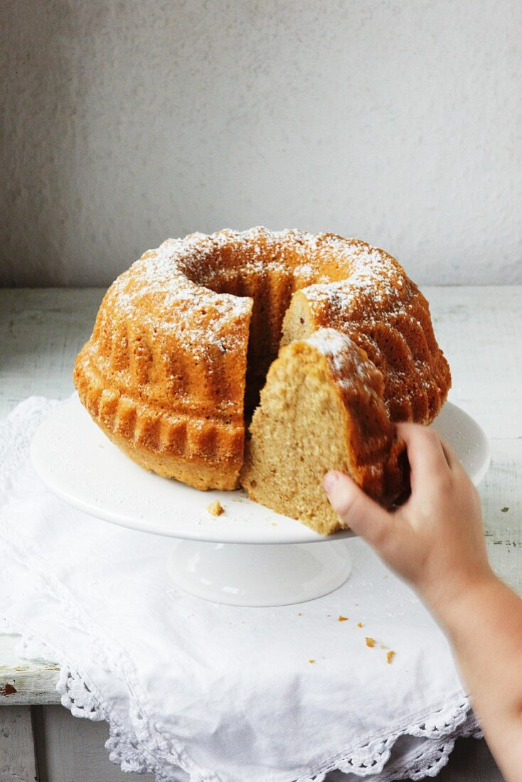 A child's hand reaching for a slice of Bundt cake