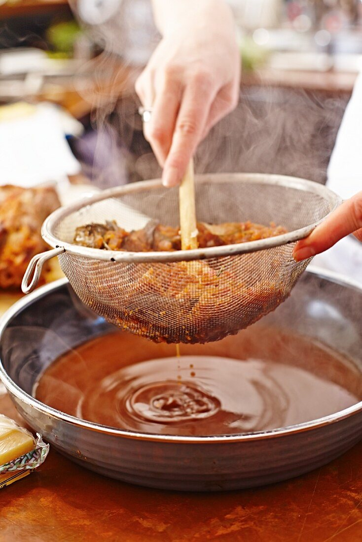 Lamb gravy being strained through a sieve