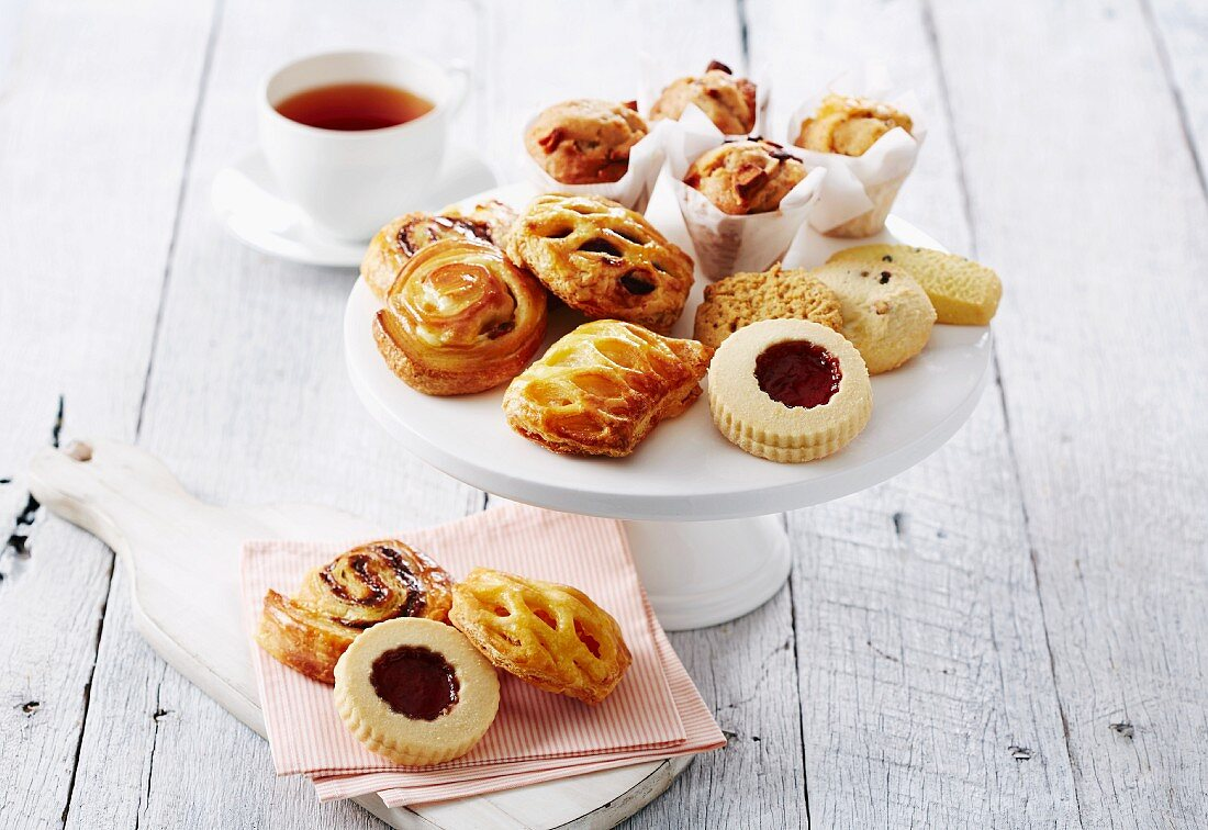 Assorted cakes, biscuits and pastries served with tea, on a cake stand and on napkins
