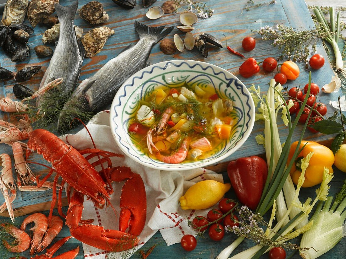 A bowl of fish soup surrounded by ingredients