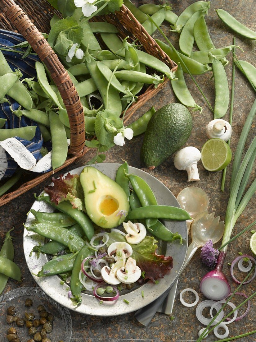 A plate of raw vegetables and sugar snap peas