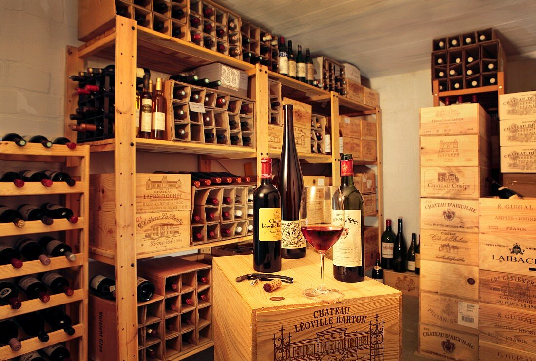 Assorted bottles of wine in wooden crates and wine shelves in a wine cellar