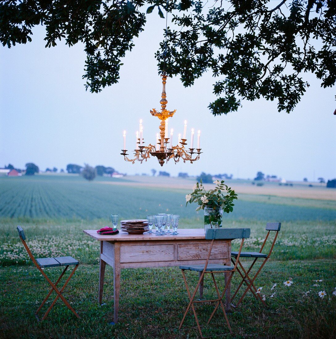 Romantic outdoor dinner with candle chandelier hanging from tree