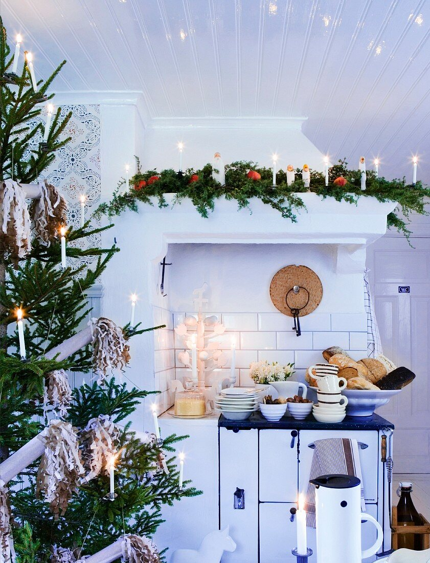 Lit candles on decorated Christmas tree in country-house kitchen and stacked crockery on cooker