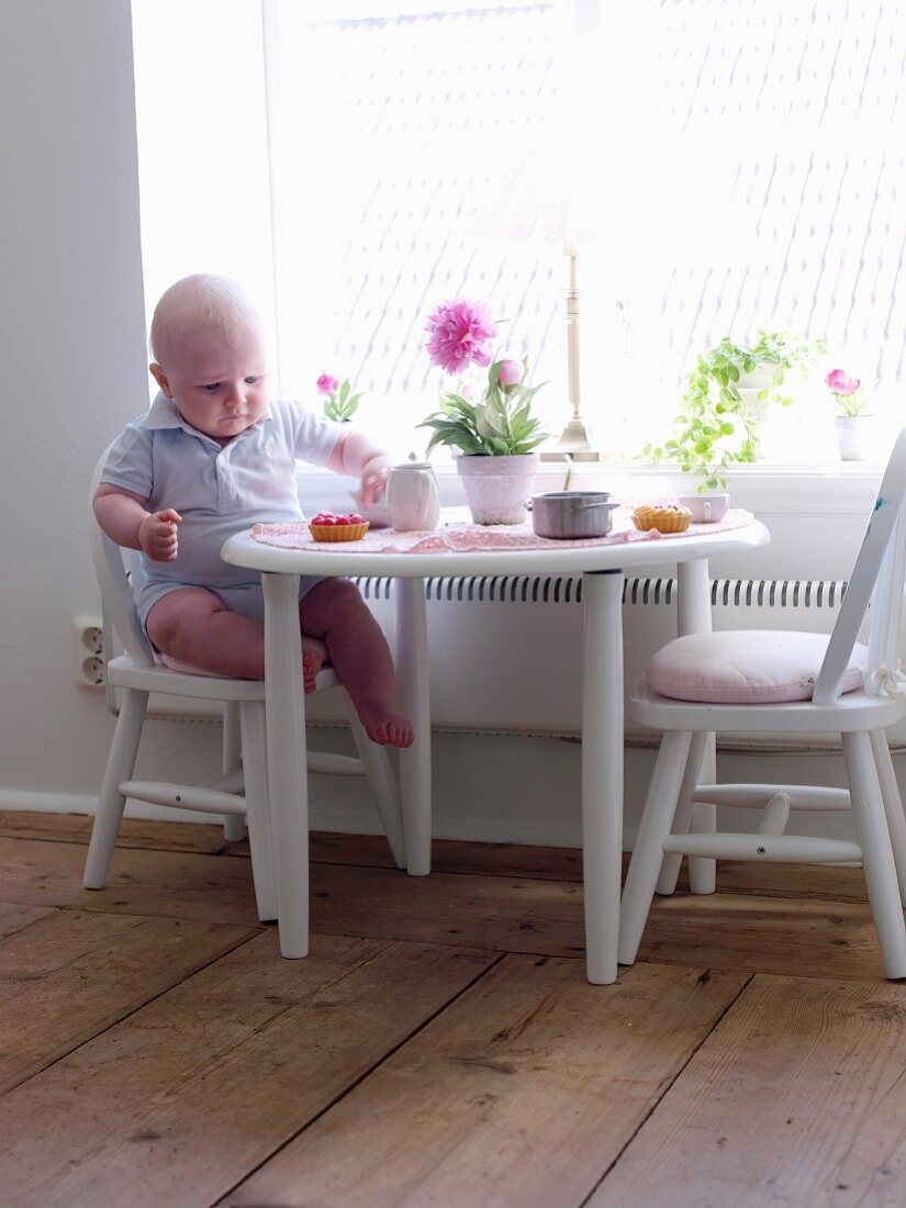 Baby sitting at table on child's chair eating tart