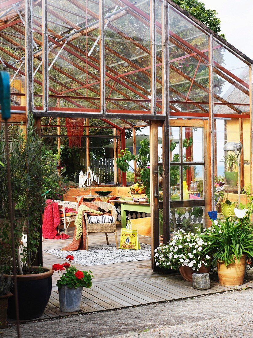View into open-plan, modern conservatory with comfortable garden furniture