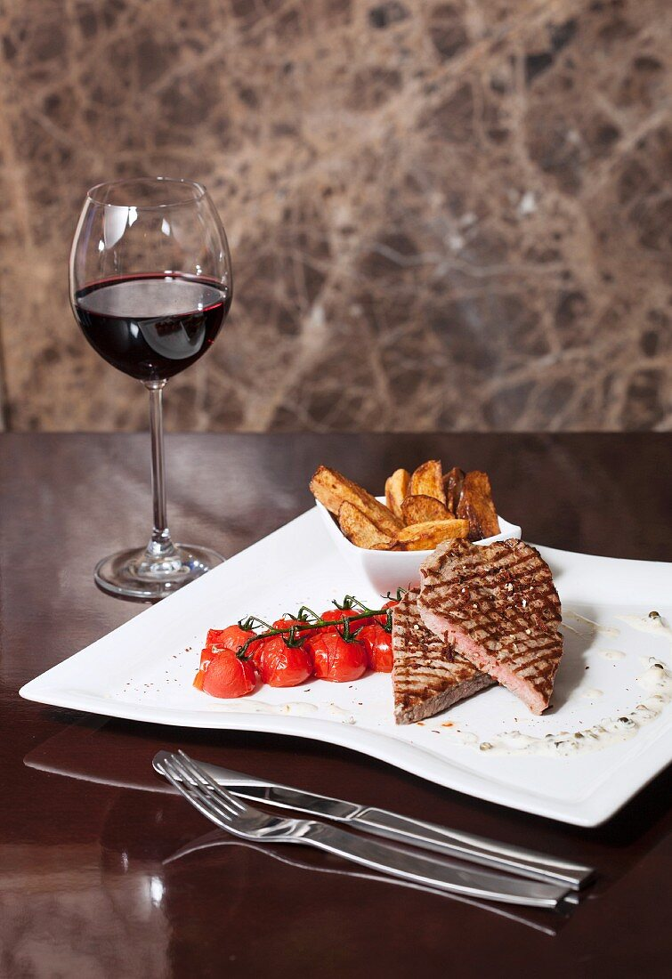 Beef steak with steamed tomatoes and fried potatoes