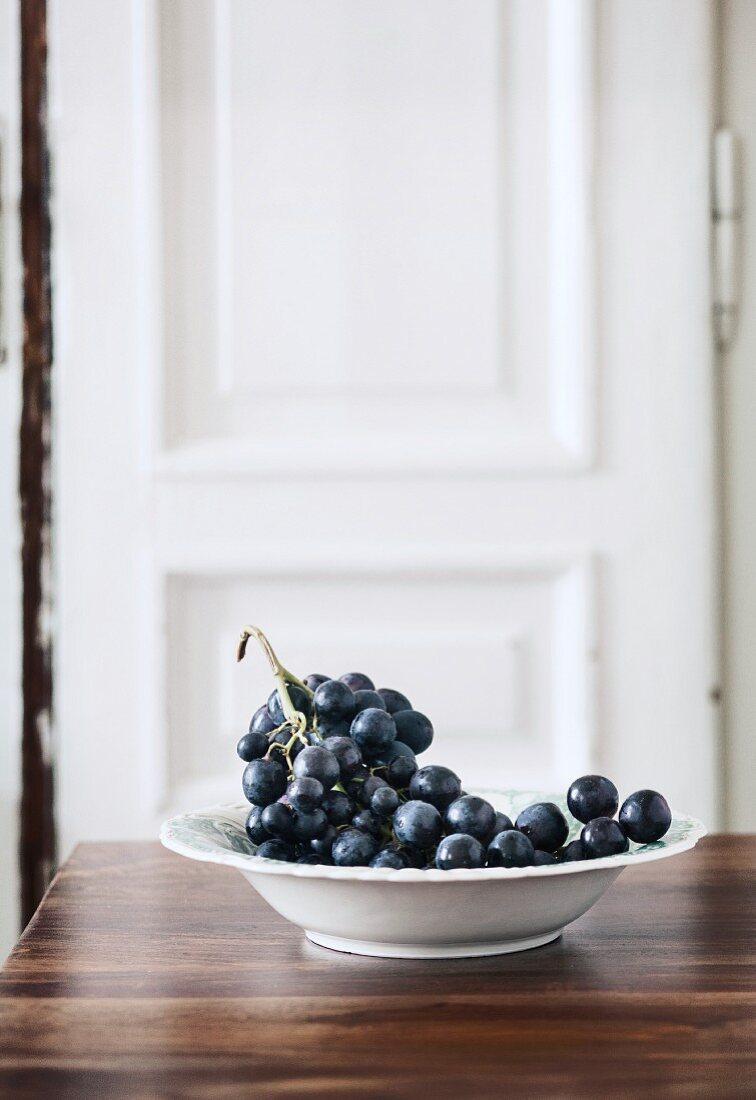 Black grapes in a white bowl