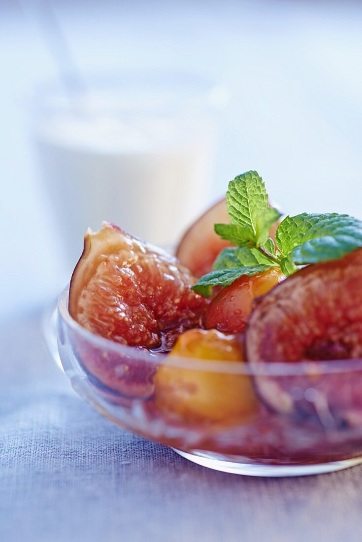 Fig and mirabelle plum compote with mint leaves