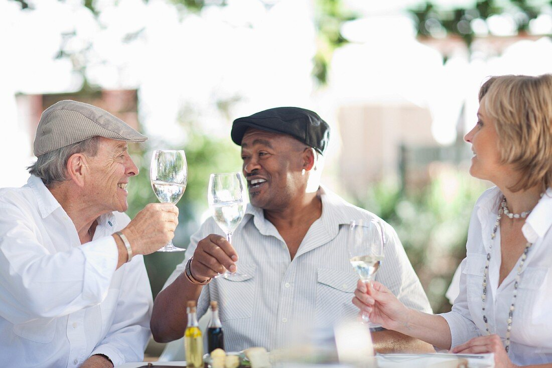 Two older men and a woman clinking their wine glasses